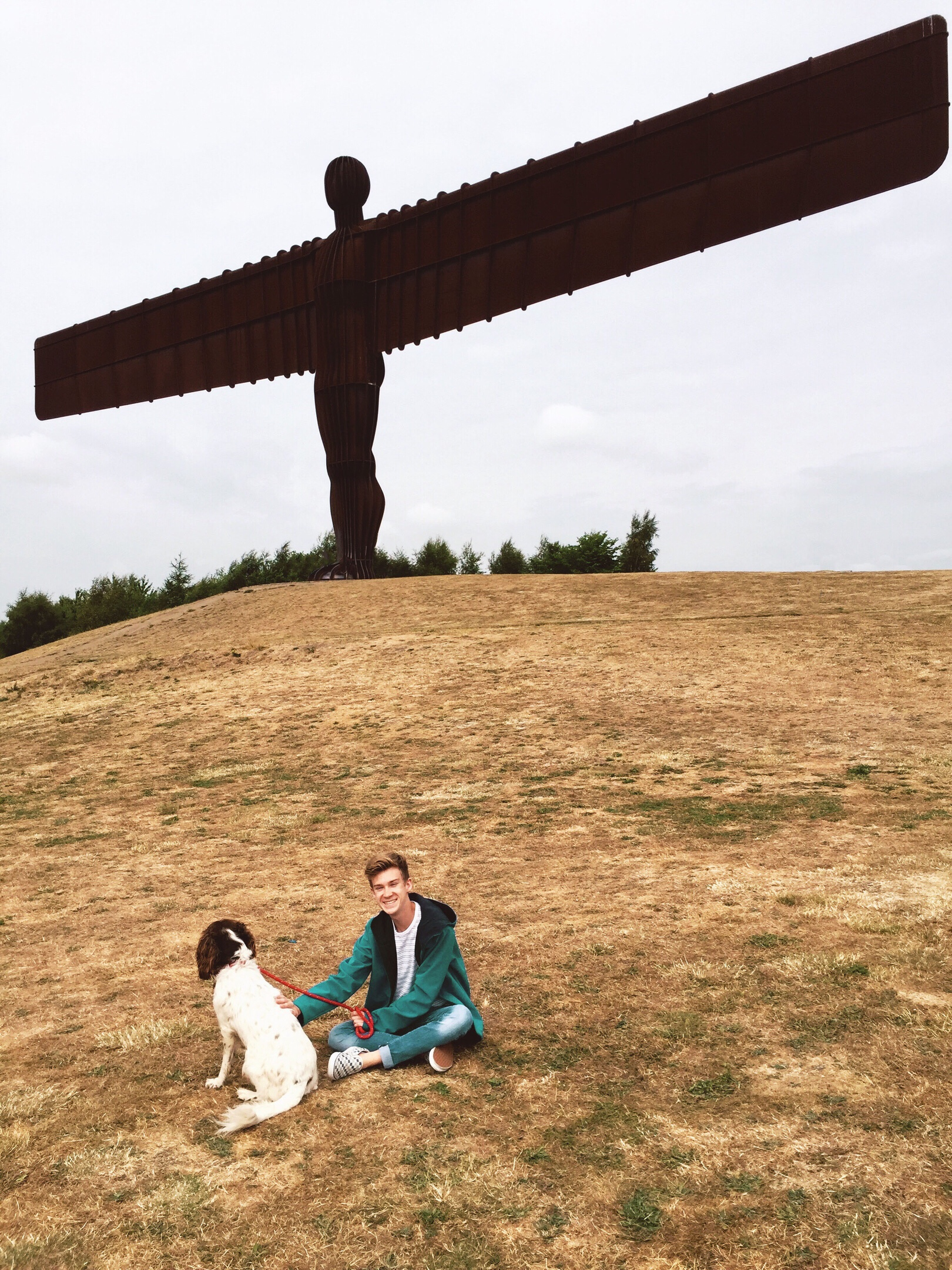 A boy sitting on the grass with a dog in front of the Angel of the North in Newcastle
