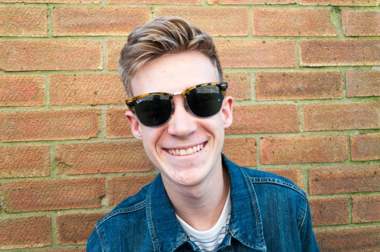 A boy wearing Ray Bans in front of a brick wall