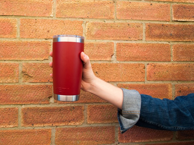 An arm holding a red Yeti Cup in front of a brick wall
