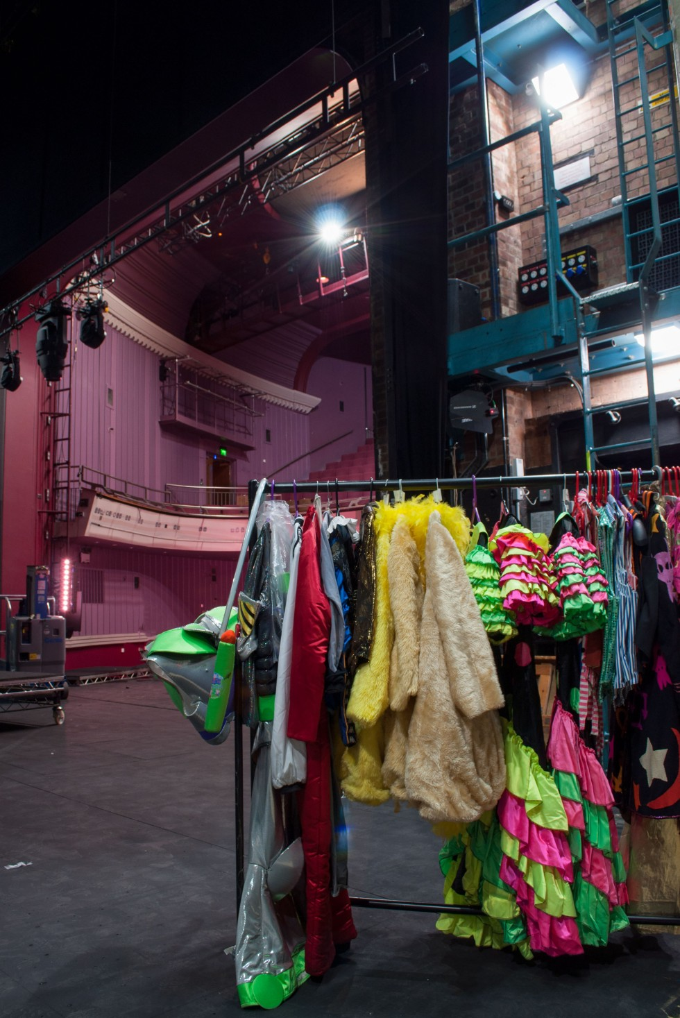 The inside of the Norwich Theatre Royal with a rack of colourful costumes on display